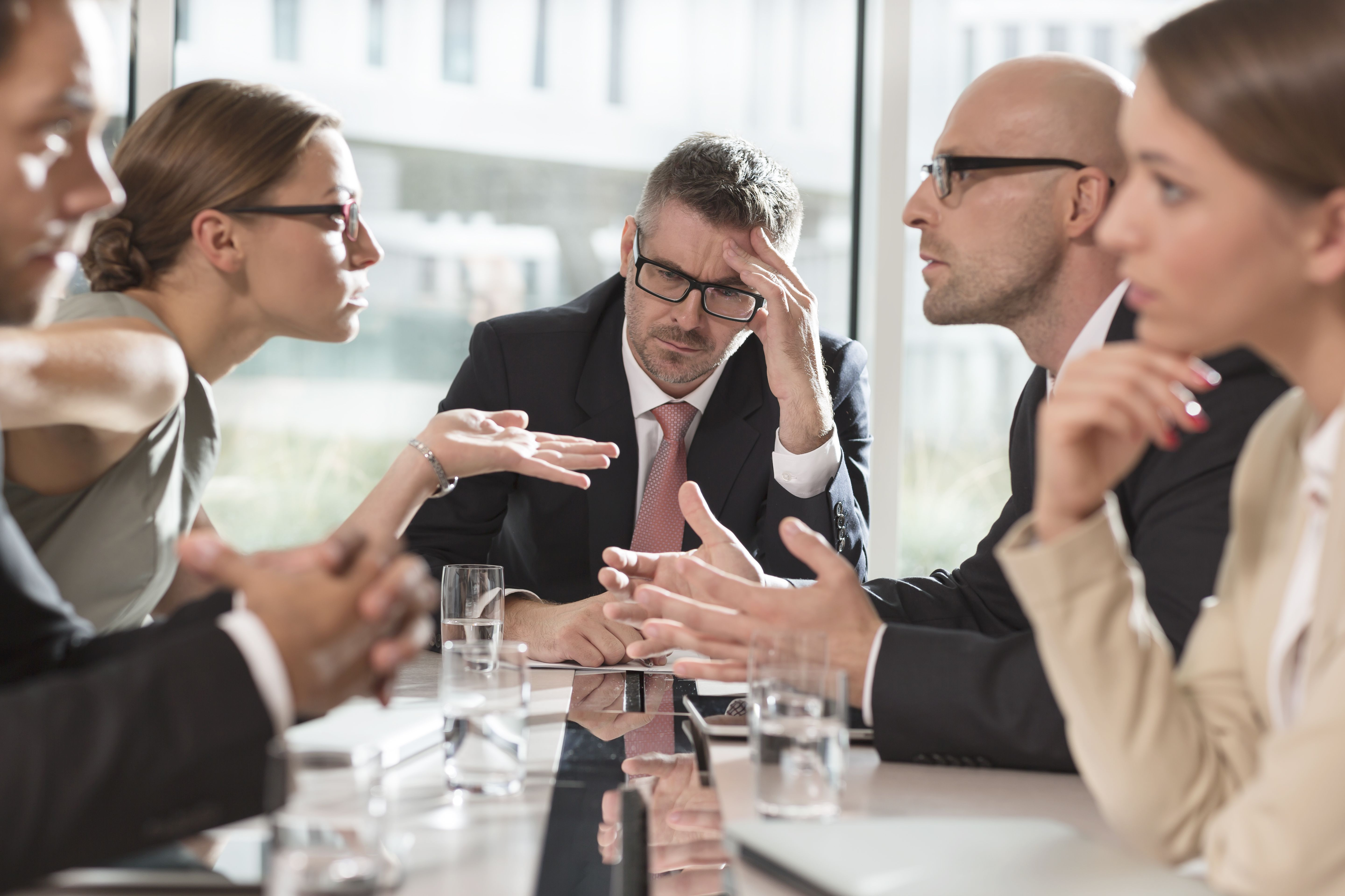 Business partners in disagreement at conference table.