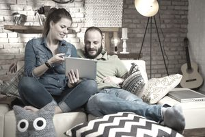 couple sitting on the sofa looking at a tablet