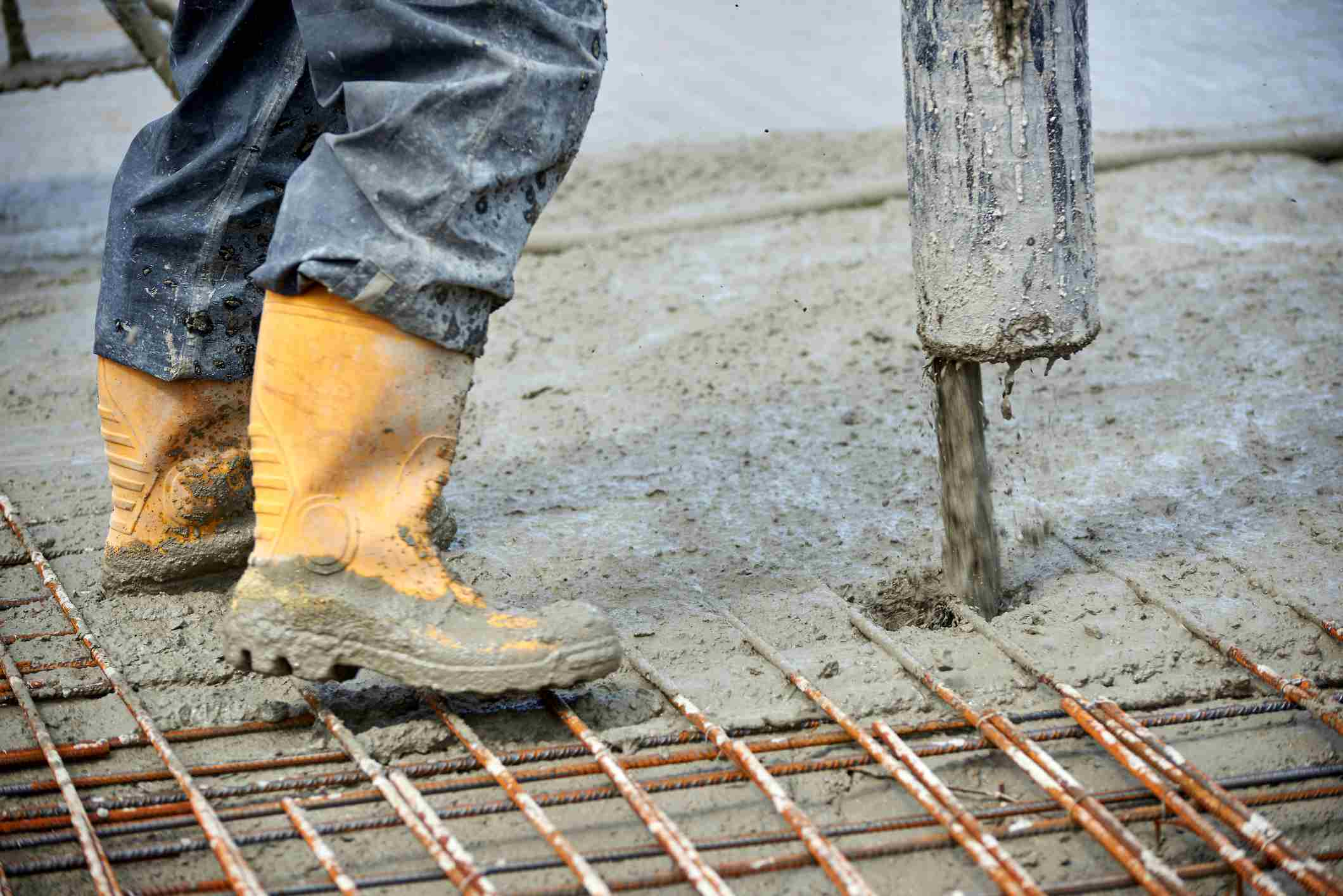 Low Section Of Worker Standing On Iron Rods At Construction Site