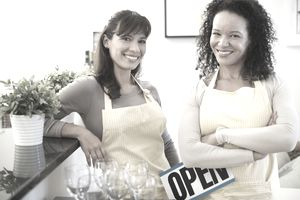 "Two women in aprons, one holding an ""Open"" sign"