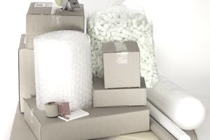 Shipping supplies, including cardboard boxes, tape, packing peanuts, and bubble wrap.