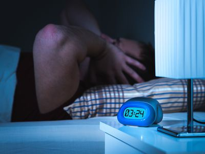 man lying awake in bed at 3:24 a.m. due to noisy neighbors, covering his ears with his hands