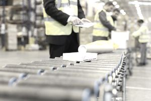 Workers checking packages on conveyor belt in warehouse