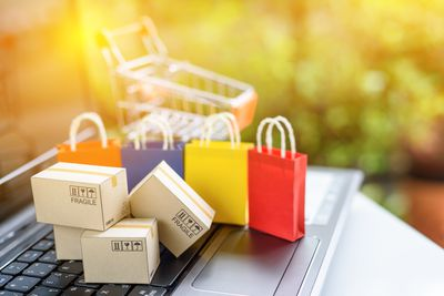 Online shopping and ecommerce via internet concept : Paper boxes and color shopping bags on a laptop computer keyboard with empty shopping cart behind. Consumer always buy things from online stores.