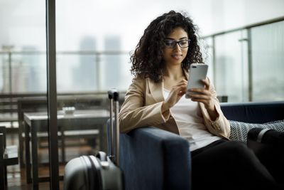 A young businesswoman is looking at her phone with a suitcase next to her.