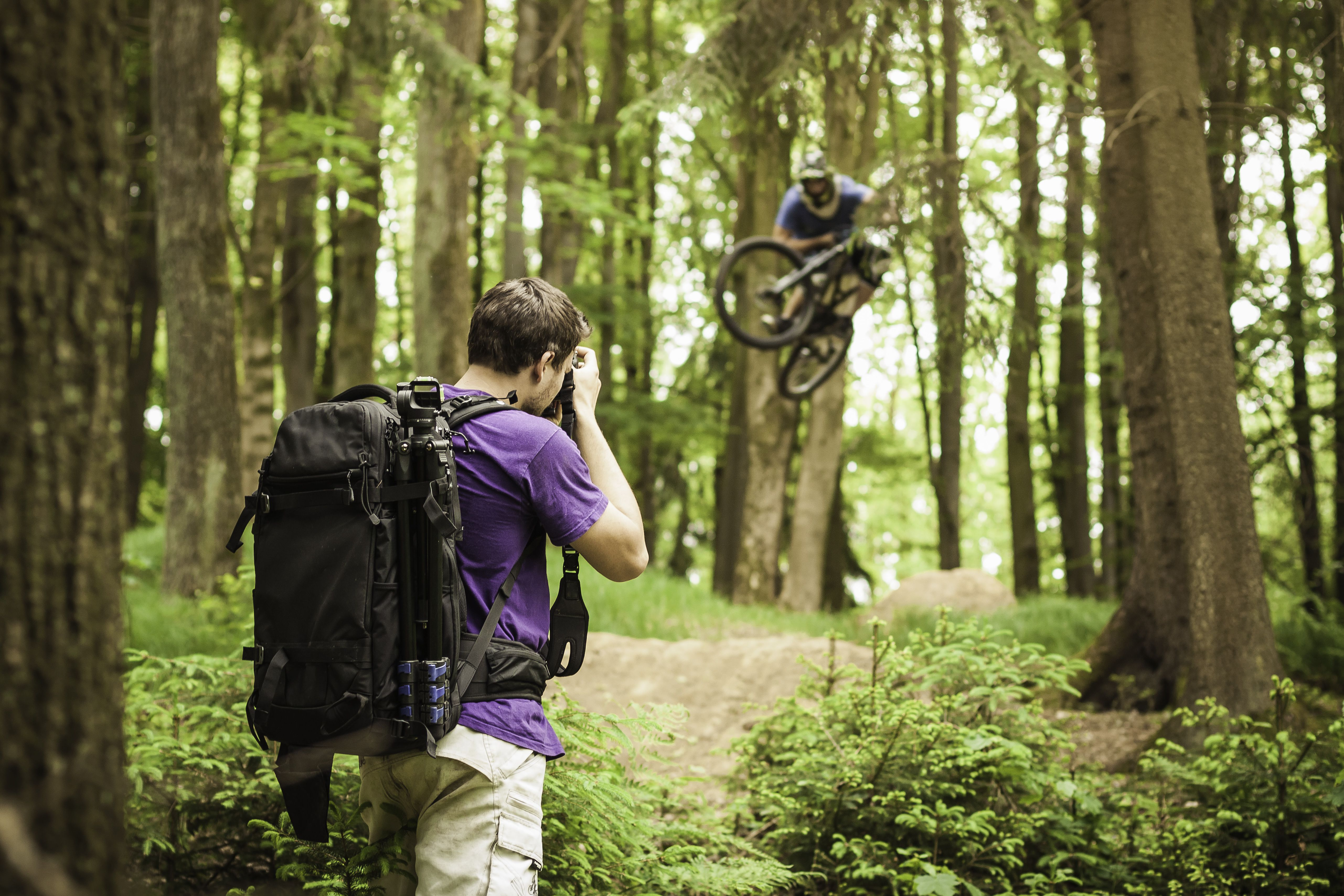 Photographer photographing mountain biker in forest