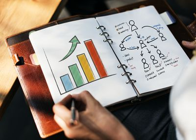 Woman drawing charts for a marketing plan in her agenda.