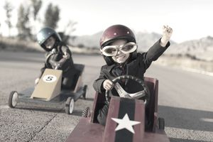 Two young boys in soapbox derby race. Winner raises fist in the air.