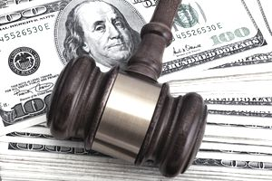 Gavel over hundred dollar bills. Financial settlement.