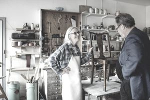 Woman showing a refinished antique chair to a man in her workshop.