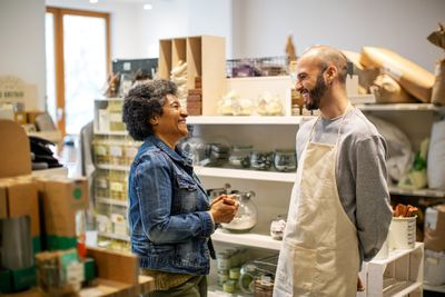 A business owner laughs with a loyal customer.