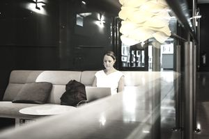 Businesswoman Sitting Working on Laptop in Hotel Bar