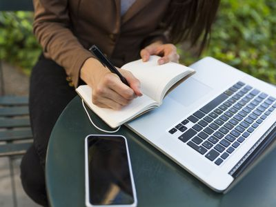 Young businesswoman with laptop sitting at table in a park making notes, partial view