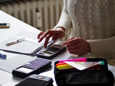 Torso of woman at a desk doing accounting with calculators, pens, and paper