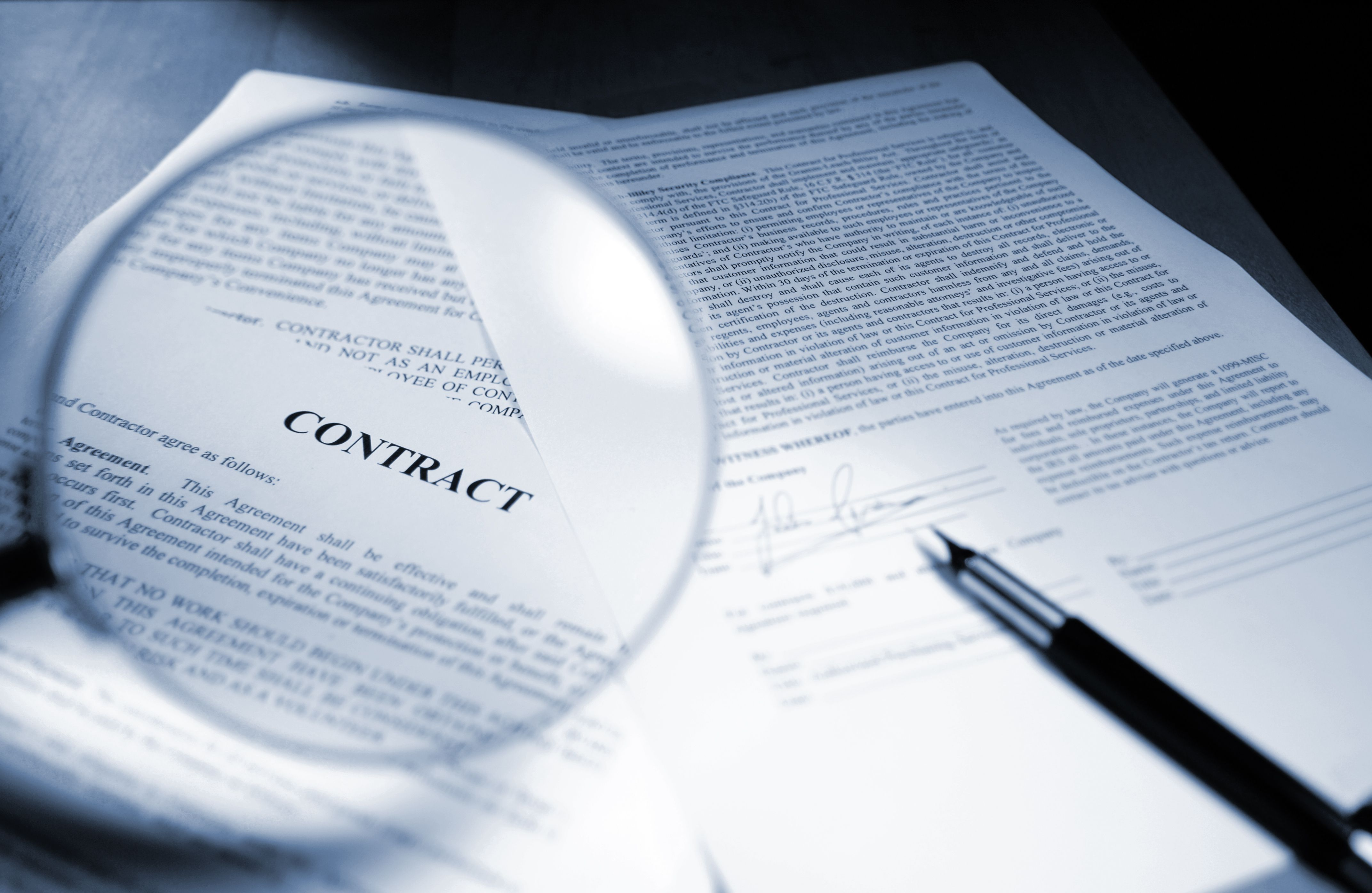 Magnifying Glass Examining Signed Legal Contract