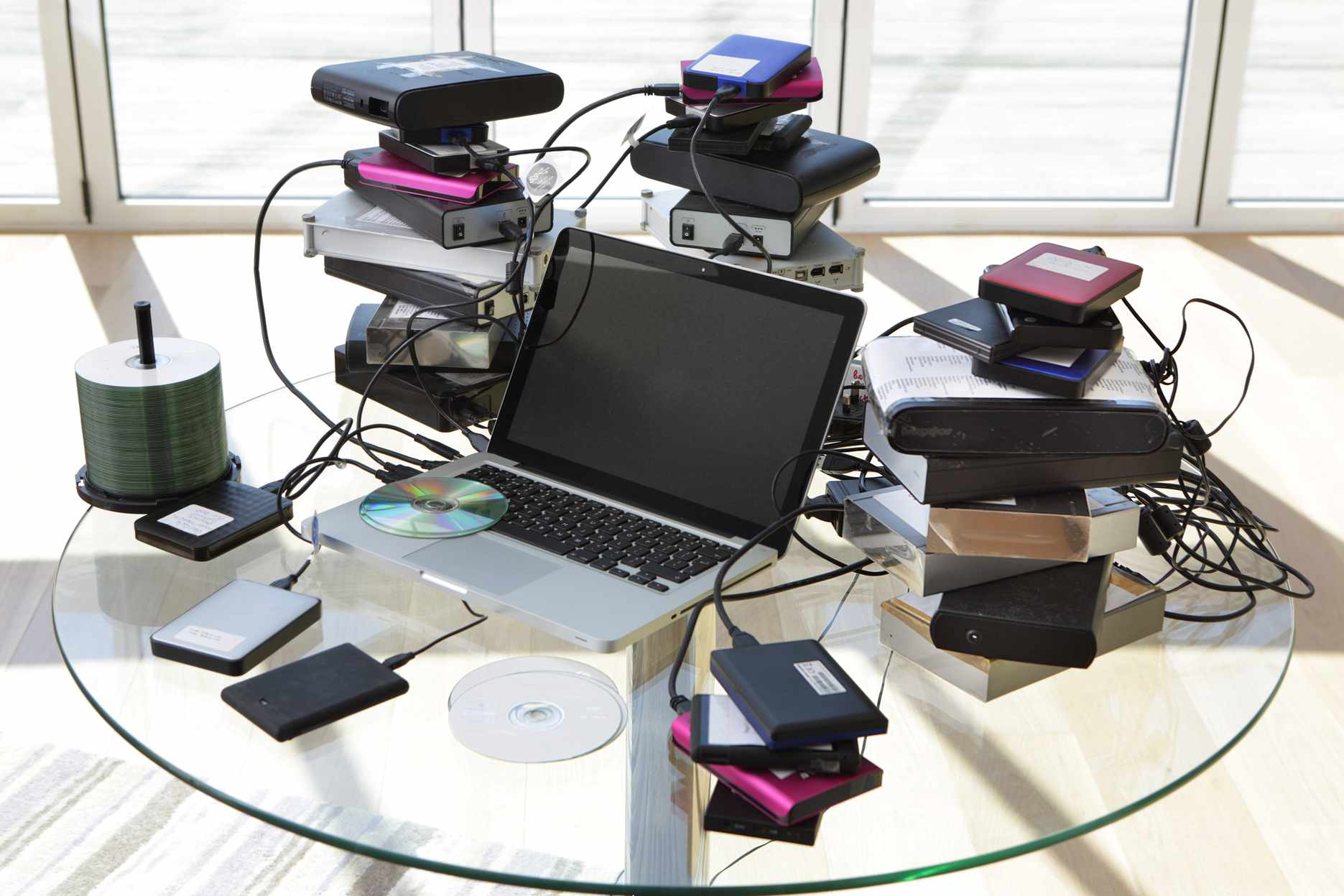 A laptop surrounded by stacks of external hard drives and discs