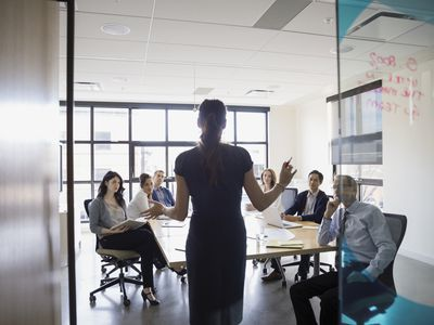 Salesperson standing in front of group in a conference room introducing their product during a 30 second presentation