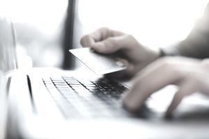 Close-up of man's hands using laptop and holding credit card