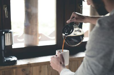 Man pouring coffee from a pot into a white mug