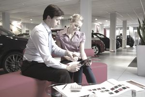 Salesman with customer in car showroom