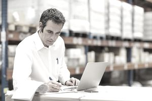 man working at laptop in warehouse