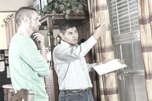 Home inspector explaining damage and repairs to homeowner