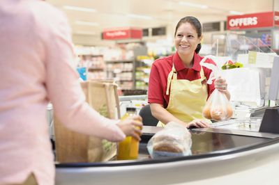 Cashier helping customer at grocery checkout