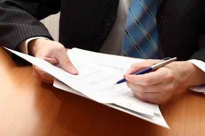 man with pen analyzing financial statement and jotting down notes