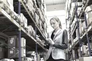 Woman using a tablet to process customer orders in a warehouse.