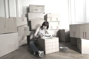 Woman sitting on floor writing on packing box