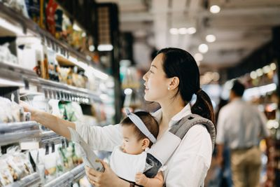 Woman holding baby while shopping in supermarket.