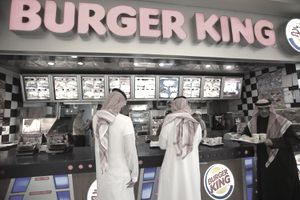 Three Kuwaiti customers ordering at the counter of a Kuwait City Burger King franchise