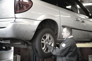 Mechanic examining car tire at auto repair shop
