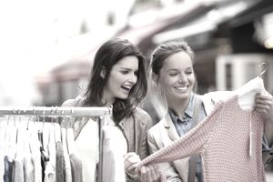 Two women shopping in a retail boutique during a special sidewalk sale event.