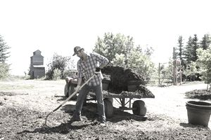 Man tilling soil; load of mulch and 4WD vehicle