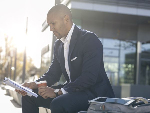 Man in a suit sitting outside reading magazine