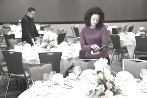 Wedding planner going over plans on tablet before reception