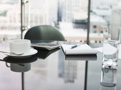 Desk with coffee, calculator, notepad and water