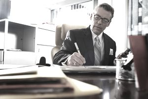 Businessman writing at desk, low angle view