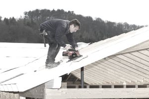 Man building a wife roof on a new house