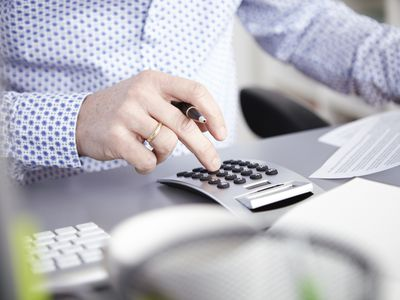 Man using a calculator to determine his business' net earnings for tax purposes.