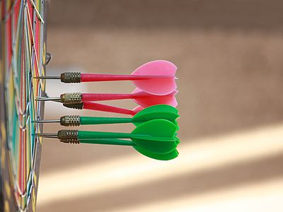 Sideview of olorful darts in dartboard