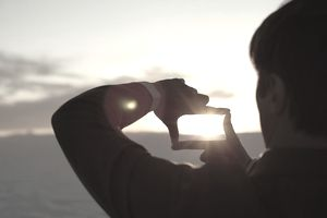 Man Framing Sunset with Fingers.