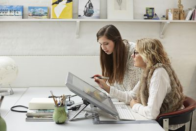 an older woman working with a younger woman intern on a computer