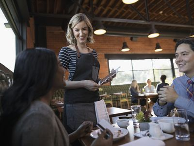 Couple dining, paying server with digital tablet