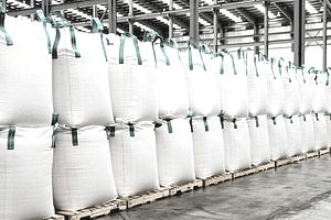Row of bulk bags (FIBC) double-stacked on pallets in a warehouse