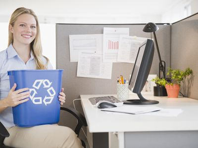 Woman holding a recycling bin in at her desk