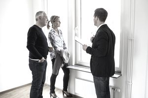 Male real estate agent discussing with sellers at home
