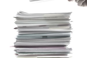 a hand holding a paper and placing it on top of a stack of documents