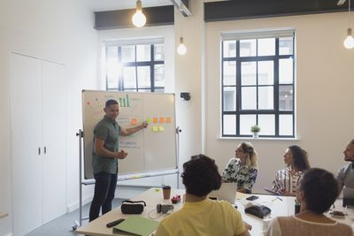 Male designer at whiteboard leading conference room meeting